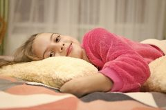 Pajamas and clothes for home. Girl little kid wear soft cute pajamas while relaxing on bed. Comfortable pajamas for stock photography