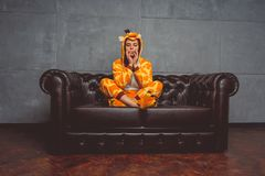 Pajamas for Halloween in the form of a giraffe. Emotional portrait of a girl on a sofa background. Crazy and funny man in a suit. Clean skin and long hair stock photo