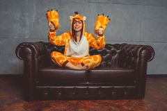 Pajamas for Halloween in the form of a giraffe. Emotional portrait of a girl on a sofa background. Crazy and funny man in a suit. royalty free stock photography