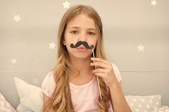 Pajamas party concept. Girl fake mustache at pajamas party. Cheerful kid posing mustache. Photo booth props ideas. Printable accessories for party. Girl long royalty free stock photography