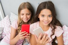 Pajamas party concept. Girlish leisure happy childhood. Girls long hair with smartphones use modern technology. Lets. Take selfie. Send photo your friends stock photo