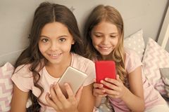 Pajamas party concept. Girlish leisure happy childhood. Girls long hair with smartphones use modern technology. Lets. Take selfie. Send photo your friends royalty free stock image