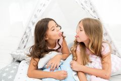 Pajamas party for kids. Sisters or best friends spend time together lay in tipi house. Girls having fun tipi house. Girlish leisure. Sisters share gossips stock photography