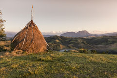 Pajar en un prado en la colina de la montaña imagenes de archivo
