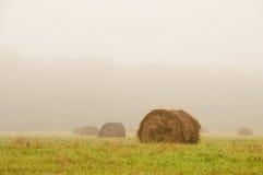 Pajar grande en un campo de niebla de la mañana Imagen de archivo