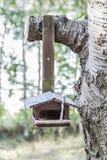 Pajarera de madera vieja clavada al árbol Foto de archivo libre de regalías
