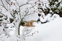 Pajarera en un árbol cubierto con nieve Fotos de archivo