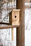 Pajarera para los pájaros en el fondo de madera Foto de archivo