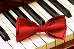 Pajarita roja en el piano Fotos de archivo libres de regalías