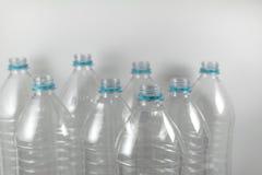 Pak bevindende Flessen van een liter en de helft van leeg mineraalwater zonder kappen enkel met de verzegelende ring op een wit stock foto