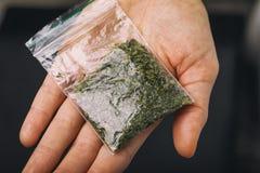 Pak droge verscheurde kruiden op de palm stock fotografie