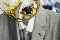 Pak met een gouden kroon die op een hanger hangen De kleding is een succesvolle persoon Bedrijfs concept metafoor royalty-vrije stock afbeelding