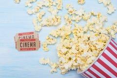 Pak popcorn bij de bioskoop en twee filmkaartjes op een blauwe achtergrond royalty-vrije stock foto