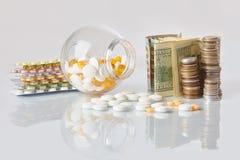Pak van geneeskundepillen met drie pakken muntstukken en glasfles met het geld van het dollarcontante geld royalty-vrije stock foto's