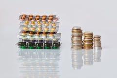 Pak van geneeskundepillen met drie pakken muntstukken en glasfles met het geld van het dollarcontante geld stock fotografie