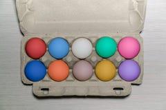 Pak van tien kleurrijke eieren Gouden ei over groene gradiëntachtergrond Geschilderde eieren Een kartondienblad met ruwe kippenei stock foto's