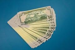 Pak van vijftig die dollarsbankbiljetten op blauwe achtergrond worden ge?soleerd royalty-vrije stock fotografie