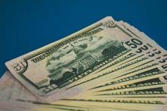 Pak van vijftig die dollarsbankbiljetten op blauwe achtergrond worden ge?soleerd stock foto's