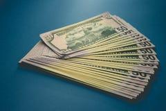 Pak van vijftig die dollarsbankbiljetten op blauwe achtergrond worden ge?soleerd royalty-vrije stock foto's