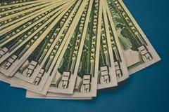 Pak van vijftig die dollarsbankbiljetten op blauwe achtergrond worden ge?soleerd stock foto