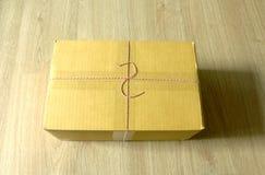 Paket in der Pappschachtel auf Holzfußboden Stockbilder