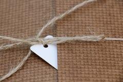 Paket gebunden mit weißer Schnur mit dem Adressen-Etikett befestigt Lizenzfreie Stockbilder