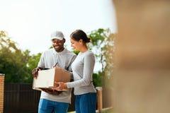 Paket-Liefern Lieferer, der Kasten an Frau liefert stockfotos