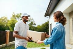 Paket-Liefern Lieferer, der Kasten an Frau liefert stockfoto
