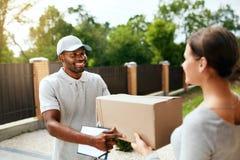 Paket-Liefern Lieferer, der Kasten an Frau liefert lizenzfreie stockbilder