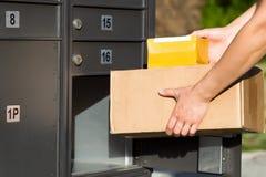 Pakete, die in Postbriefkasten geladen werden lizenzfreie stockfotos