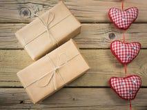 Pakete eingewickelt im braunen Papier und in der Schnur mit Herzen Lizenzfreie Stockbilder