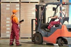 Pakhuis en opslag de werken van pakhuisarbeiders met vorkheftrucklader stock foto
