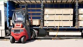 Pakhuis Het leegmaken van de vrachtwagen Het leegmaken van goederen van de vrachtwagen aan het pakhuis De vorkheftruck zet lading stock videobeelden