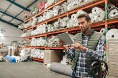 Pakhuisarbeider die een digitale tablet gebruikt om voorraad te controleren royalty-vrije stock foto's