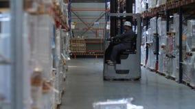 Pakhuisarbeider die een vorkheftruck berijden 4K langzame mo stock videobeelden