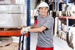 Pakhuisarbeider die Handtruck met Karton duwen Stock Foto