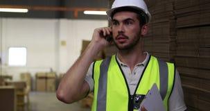 Pakhuisarbeider die op het klembord van de telefoonholding spreken stock video