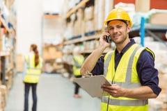 Pakhuisarbeider die op het klembord van de telefoonholding spreken Royalty-vrije Stock Foto