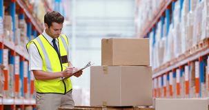 Pakhuisarbeider die pakketten bekijken stock footage