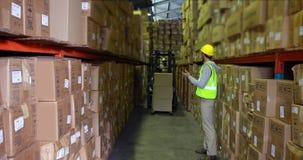 Pakhuisarbeider die vorkheftruckbestuurder leiden stock video