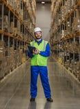 Pakhuisarbeider die zich tussen rijen met dozen bevinden royalty-vrije stock foto