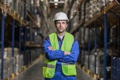 Pakhuisarbeider die zich tussen rijen met dozen bevinden royalty-vrije stock fotografie