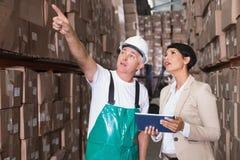 Pakhuisarbeider en manager die tabletpc met behulp van royalty-vrije stock foto's