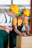 Pakhuisarbeiders die aantal dozen controleren stock afbeelding