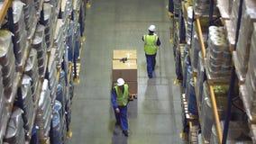 Pakhuisarbeiders die tussen rekken met koopwaar lopen stock footage
