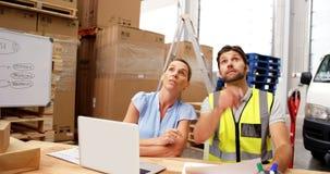 Pakhuisarbeiders gebruikend laptop en richtend planken stock video