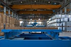 Pakhuisbinnenland met sommige goederen en machines stock afbeeldingen