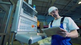Pakhuiseenheid met een mannelijke arbeider die een controlerend paneel in werking stellen stock videobeelden