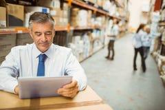 Pakhuismanager die aan tabletpc werken Stock Foto's