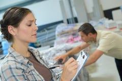 Pakhuismanager die inventaris in groot pakhuis controleren royalty-vrije stock fotografie